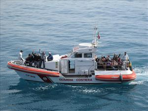 Syrian refugees are transported ashore at Sicily after disembarking the <i>Liberty Grace</i>.