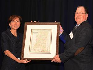 Trang Cormack, sponsor of the <i>Magnolia State</i>, presents a map of Mississippi as a gift for the ship to Captain Robert Cates following the ship's christening on April 23.