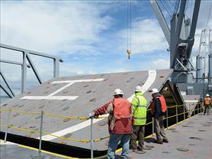 Chief Mate Richard Minutello (third from left) monitors the closure of the three-hold hatch cover on the deck of the <i>USNS Bob Hope</i> after the transfer of 150 containers of relief cargo to military lighterage was completed near Indian Island.