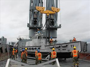 A military utility boat is prepared to be lifted from the deck of the <i>USNS Bob Hope</i> and deployed in the water for JLOTS 2016. Photo courtesy of Military Sealift Command
