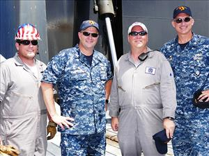 Captain Michael Sands and Chief Mate Joshua Jordan greet MPSRON 3 Commodore Captain Eric Lindfors and MSC Far East Commodore Captain Stephen Fuller aboard the <i>USNS Montford Point</i>.