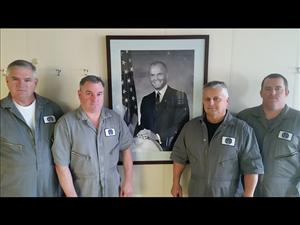 American Maritime Officers members Captain W.G. McCullough, Chief Engineer Gregg Daley, First Assistant Engineer Henry Matuszynski and Chief Mate Colin Adler gather at the portrait of John Glenn onboard the <i>USNS John Glenn</i>.