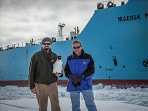 Chief Engineer James Cook and Captain Chris Fox stand in front of the <i>Maersk Peary</i> with the ship's stuffed toy mascot at McMurdo Station in February.