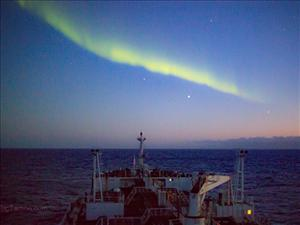 The Southern Lights illuminate the night as the <i>Maersk Peary</i> sails to Antarctica.