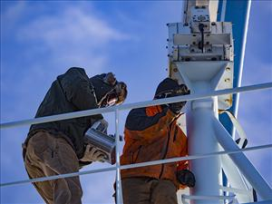Chief Engineer James Cook and Chief Mate Joshua Squyres work on <i>Maersk Peary</i>'s radar scanner.